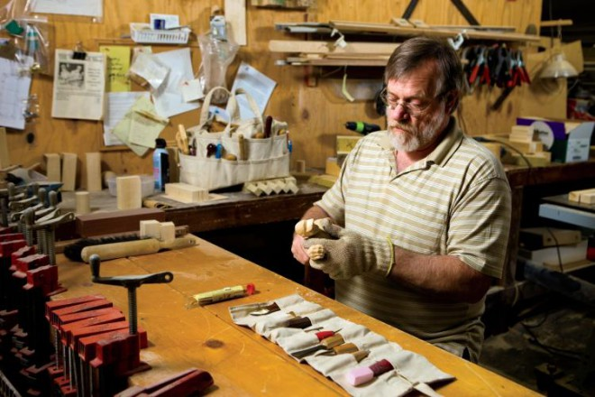 Rick Frels works on a woodcarving of a baseball player. Frels' work ranges in size from the very small to large pieces carved out of tree trunks