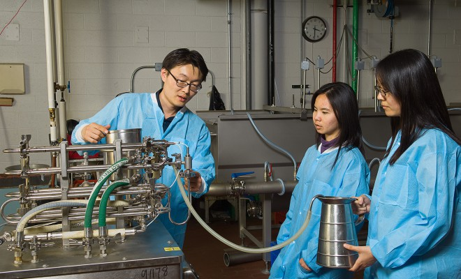 Youngsoo Lee with ultra-high-temperature processing unit. Quaker Oats donated the machine to University of Illinois ACES.