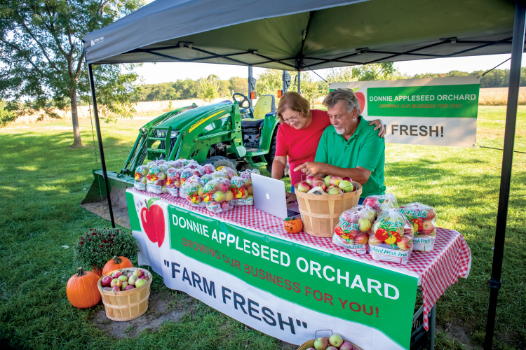 Don and Wendy Wenzel working on their digital marketing at their fruit stand in between customers. LaSalle County Farm Bureau members Don and Wendy Wenzel run a 100-acre, third-generation family farm called Donnie Appleseed Orchard, which has 250 apple trees along with 5 acres of fresh produce, including garlic, onions, green beans and tomatoes. They sell their produce at three area farmers markets, as well as their farm/orchard. What makes them stand out from the crowd is how they communicate with their customers – and broaden their reach – using social media. Their email newsletter offers coupons and provides recipes using in-season produce, and they use an app called FarmFan that lets customers get real-time updates on market days about produce availability, and also offers loyalty discounts. They're also active on Facebook and Pinterest.